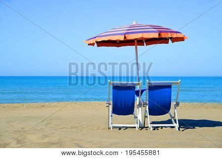 Pair of sun loungers and sunshade umbrella on the beach. Vacation concept.