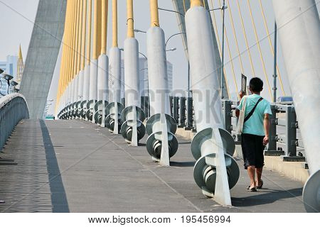 A man walking on the cable bridge.