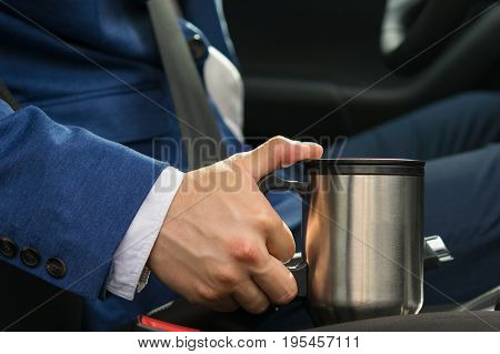 The driver in the car takes a thermos mug with a coffee bar so as not to fall asleep at the wheel