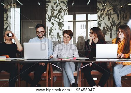 Joyful Team Of Coworkers Working Together In Modern Loft Space On The Wood Table With Contemporary L