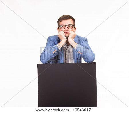 Young pensive man portrait of a confident businessman showing presentation, pointing paper placard gray background. Ideal for banners, registration forms, presentation, landings, presenting concept.