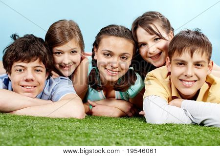 Portrait of five lying friends looking at camera and smiling