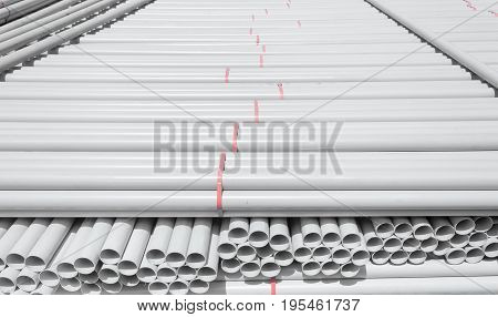 white PVC pipes stacked in warehouse .