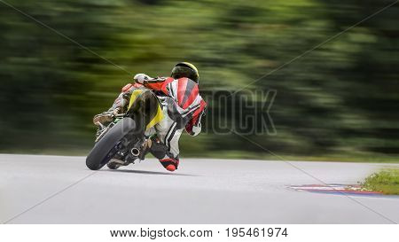 Motorcycle practice leaning into a fast corner on track.