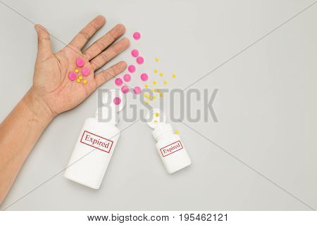 Expired drug on elderly hand on white background