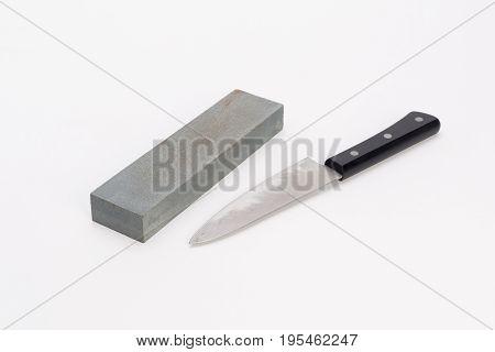 Whetstone and knife on white background on white background