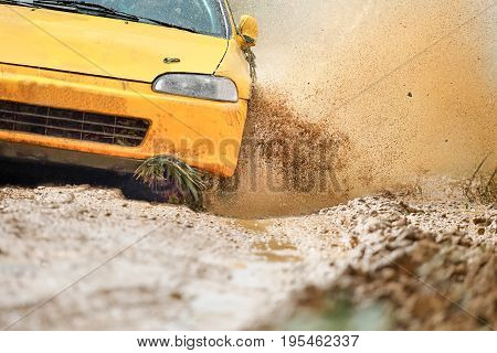 Yellow Rally Car in dirt track .