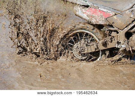 Enduro wheel in muddy track ,climb wood obstacle .