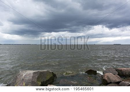 stones in the water on the coast sailboats on the horizon the Gulf of Finland the rain clouds