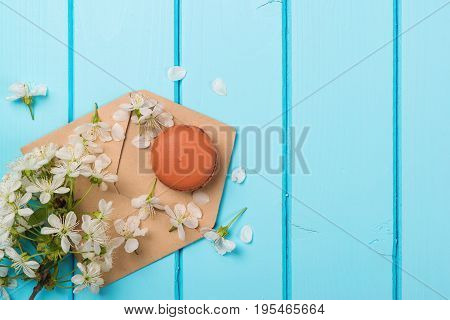 Envelope With Spring Flowers And One Macaroon On Blue Wooden Background. Top View. Copy Space