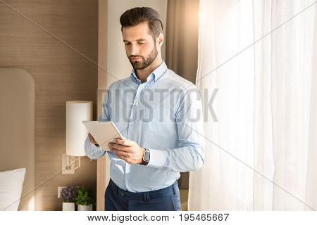 Young male business traveler hotel accomodation using tablet