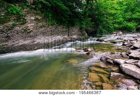 Powerful Green Forest Stream Under The Cliff