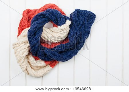 Colorful Woolly Hat And Scarf On White Wooden Background.