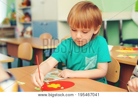 Cute Little Boy Engaged In Art And Craft In Classroom . Learning And Education Concept.
