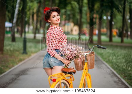 Pinup girl on retro bicycle with backet of flowers