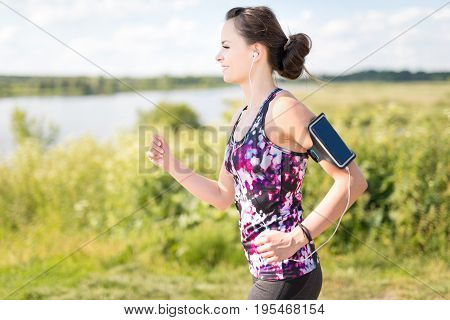 Beautiful young woman running on the water's edge by the country road. Jogging concept.