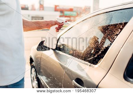 Man rubbing vehicle with car polish
