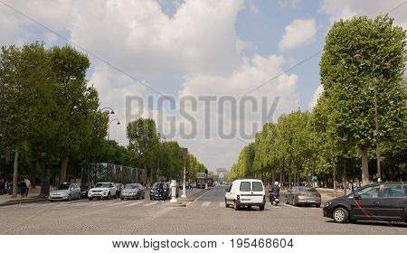 ParisFrance- April 29 2017: Tourists are walking along the Champs Elysees vehicles are moving