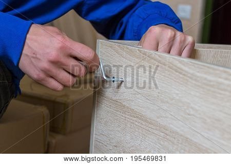 Man mounting furniture fixing using a hex key