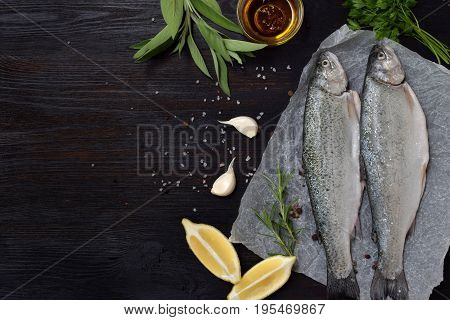Two River Trout On A Board, With Herbs, Spices, Lemon And Pepper On Wooden Board, Ready For Cooking.