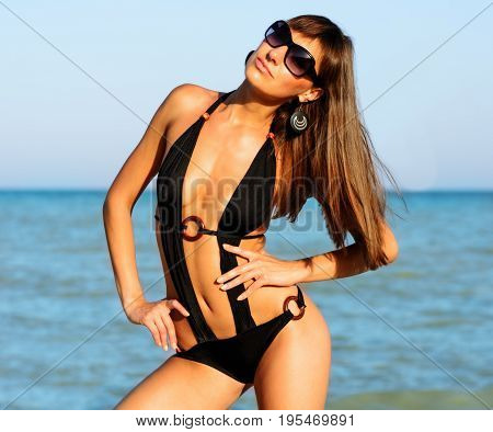 Beautiful Long Hair Young Woman In Black Swimwear And Sunglasses On The Sea Coast Beach, Close Up Ou