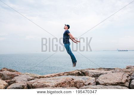 Young man jumping upwards portraying a flight against the background of the sea and sky. The concept of freedom. Life style. Travel, activity.