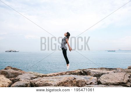 Young beautiful girl jumping upwards portraying a flight against the background of the sea and sky. The concept of freedom. Life style. Travel, activity.