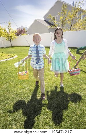 Two cute kids enjoying an Easter Egg Hunt Outdoors