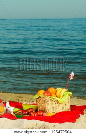 Relaxation during summertime concept. Picnic basket with fruit on red blanket near sea
