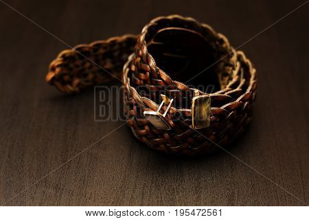 Male brown belt with cuff in wooden background