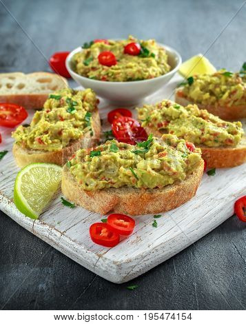 Homemade Guacamole toast with chili pepper, parsley on white wooden board.