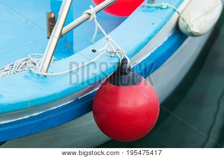 Red buoy for protecting moored yachts in marina.