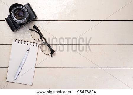 White Set. Pen, Eyeglasses And Camera On Table. Top View.