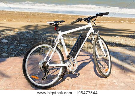 Black bicycle parked in the beach sand.