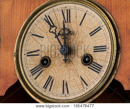 Old clock show five minutes to midnight