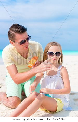 Father applying sun cream to daughter nose.