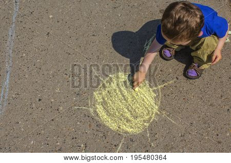 boy painting sun with colorful chalks outdoors in summer. Kid having fun. Creative leisure with children outdoors.
