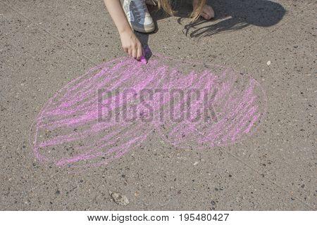Gilr paints the heart on the asphalt