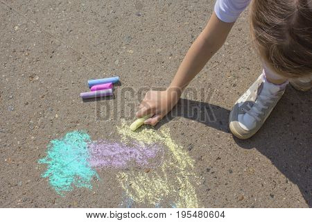Girl paints the palm on the asphalt