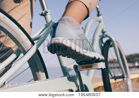 Female Foot In A Blue Sneaker And A Bicycle On The Beach