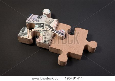 American dollar banknote over jigsaw puzzle with copy space. American dollar concept of teamwork for success, economic capital and economic investment.