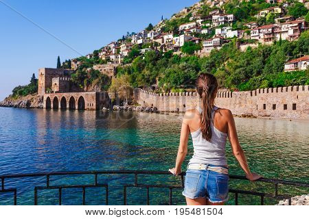 Young Woman Look On Ancient Shipyard Near Of Kizil Kule Tower In Alanya Peninsula, Antalya District,