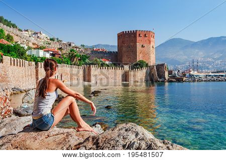 Young Woman Look At Kizil Kule Tower In Alanya Peninsula, Antalya District, Turkey, Asia. Famous Tou
