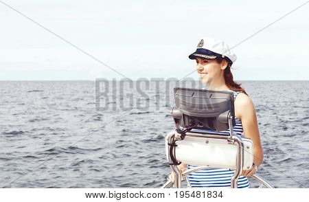 Beautiful, attractive sailor girl driving a boat. Sea, navigation concept.