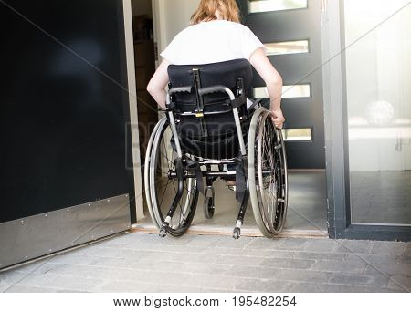 Person In A Wheelchair Moving Over A Low Doorstep