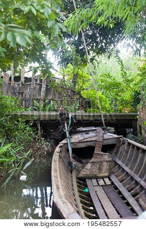 Old Wood home made engine fisher boat on Vietnam Mekong Delta Village close to a wooden walkway and village