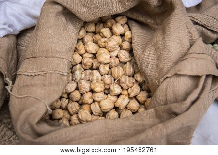 Chickpea in sack legumes. Chickpeas grains on a rustic cloth bag. Agriculture and harvest.