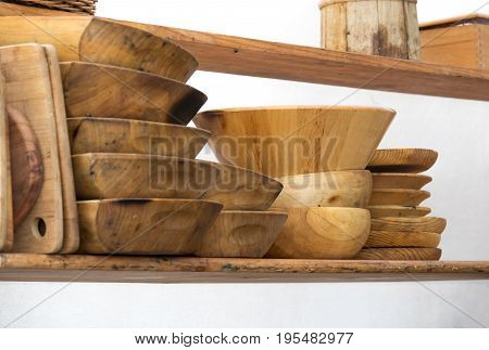 Set of rustic wooden dishes, on a kitchen shelf, isolated on white background. Dish, kitchen bowl