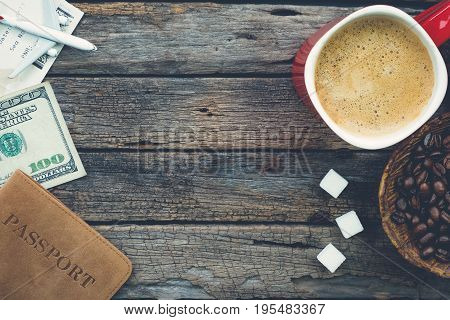 Preparing to travel with coffee coffee beans sugar cubes passport plane dollar banknote on rustic wood background