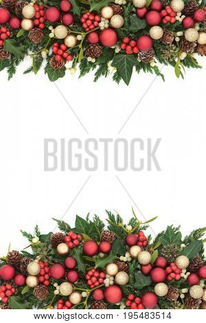 Festive christmas background border with red and gold bauble decorations, holly, ivy, mistletoe, fir and pine cones on white.